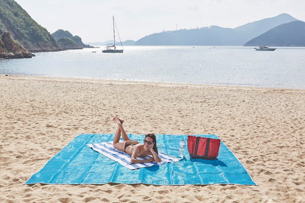 Woman Using A Sand-Free Beach Mat On The Beach